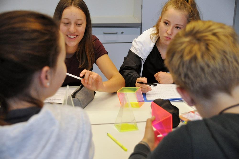 4 Mädchen arbeiten gemeinsam in einer Gruppe um einen Tisch herum an einem Projekt mit geometrischen Figuren.