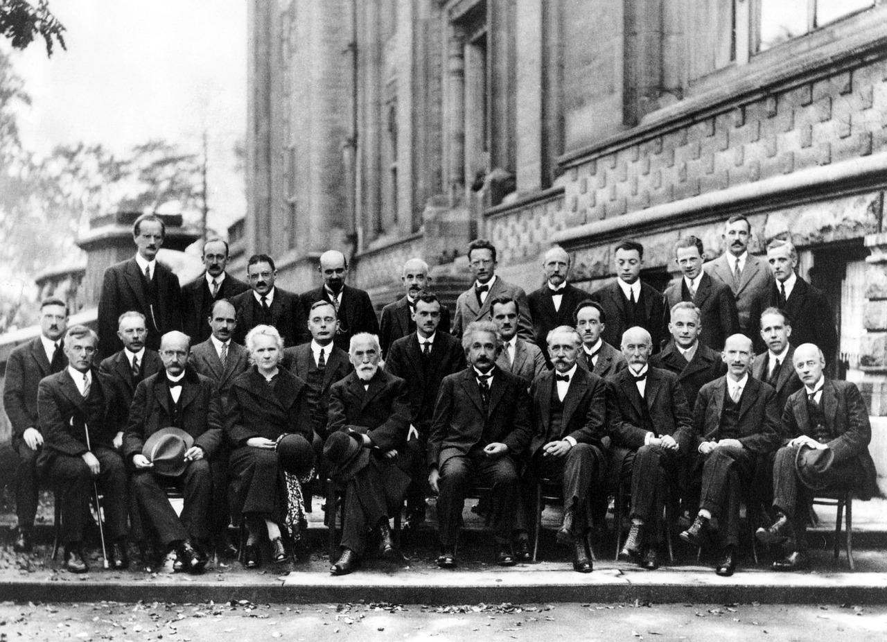Foto einer Konferenz in Solvey aus dem Jahre 1927. Abbildung zeigt berühmte Wissenschaftler, die ausschließtlich Männer sind in Anzügen. In ihrer Mitte vorne sitzt Albert Einstein. Zwei Stühle links von ihm als einzige Frau Marie Curie.